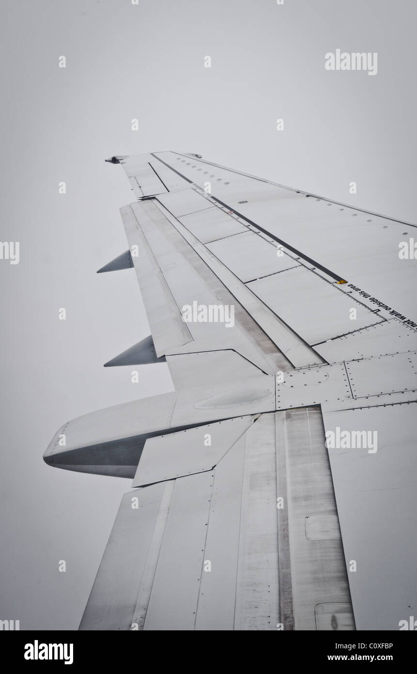 airplane wing in thick cloud - Stock Image