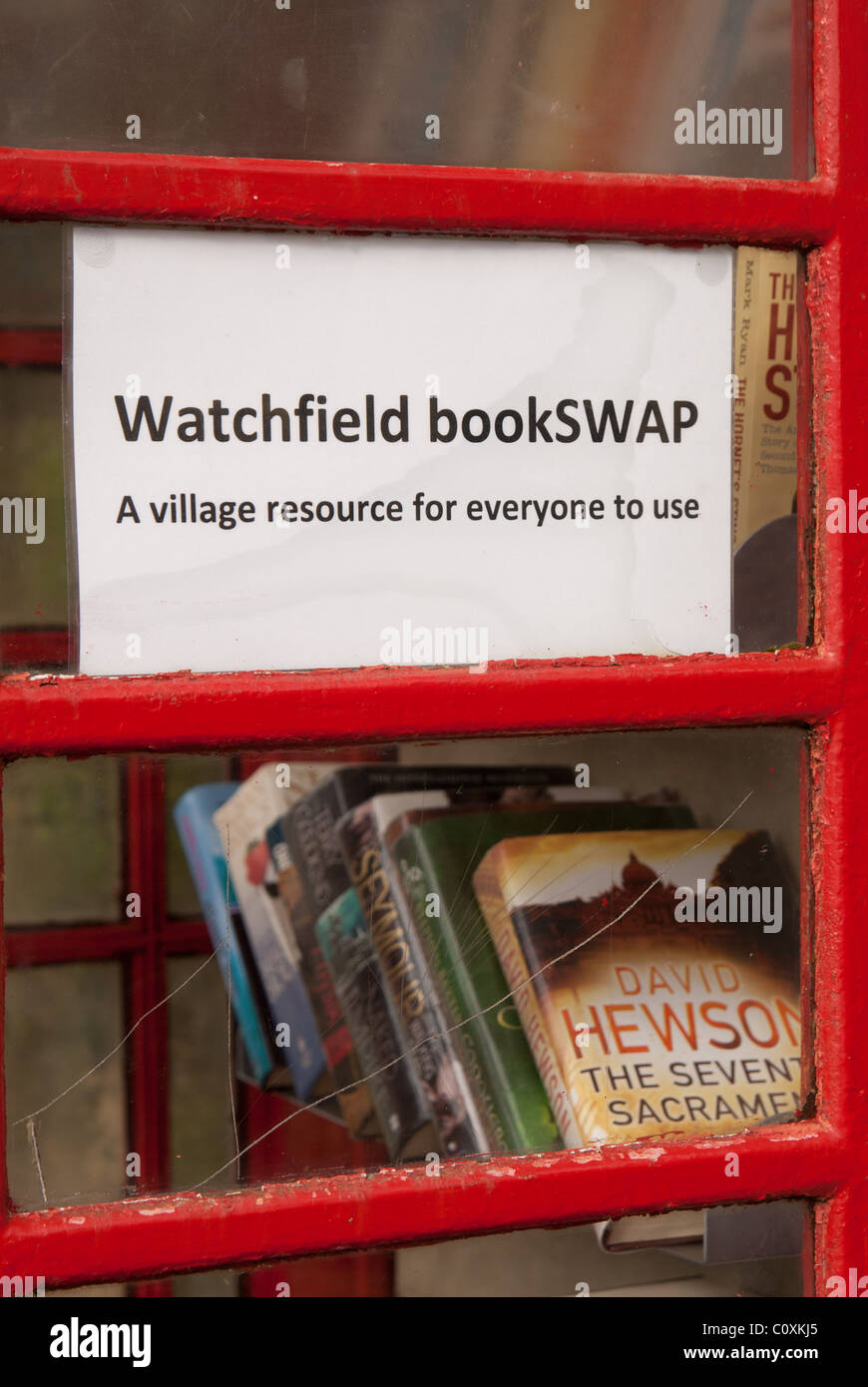 A UK village's redundant BT red telephone box now adopted by the parish council, and converted into a 'Bookswap' - Stock Image