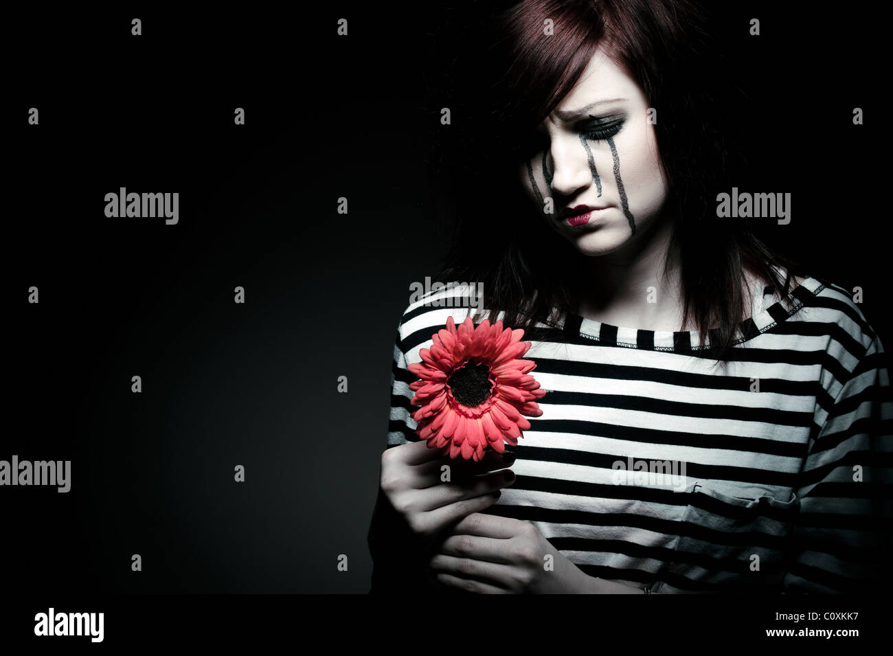 a sad female mime clown with a red flower - Stock Image