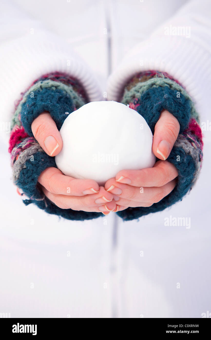 A girl wearing fingerless gloves holding a snowball - Stock Image