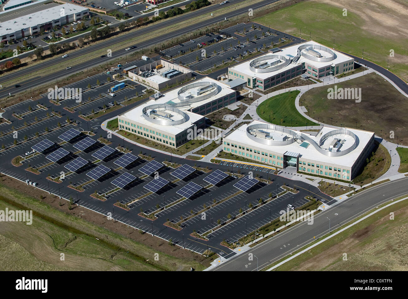 aerial view above solar panels placed in parking lot commercial office building Vacaville California - Stock Image