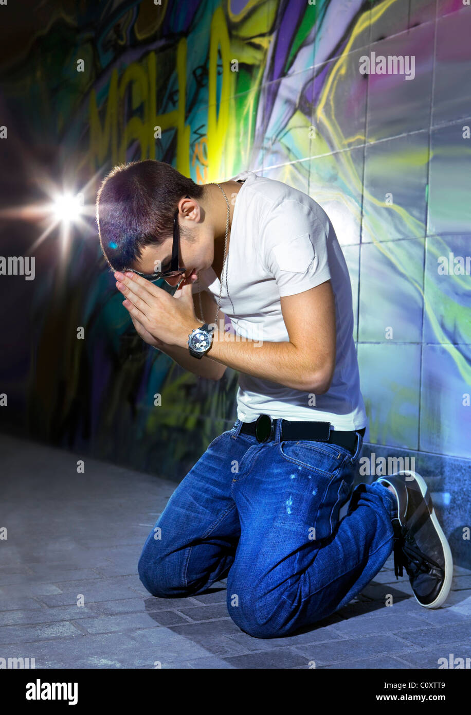 young man offers prayers in front of colorful graffiti wall - Stock Image