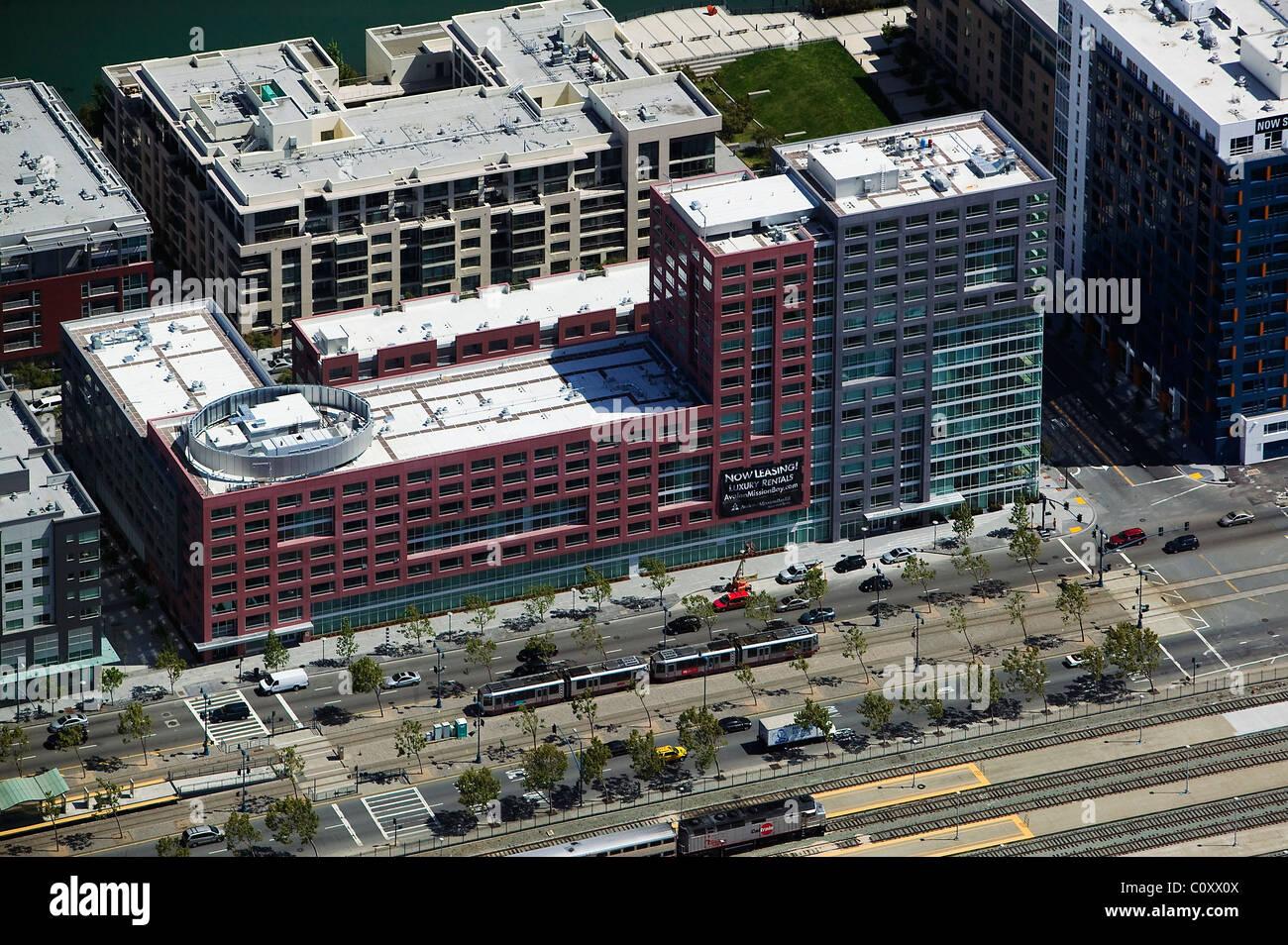 aerial view above San Francisco Muni Light Rail tracks trains at residential condominium buildings - Stock Image
