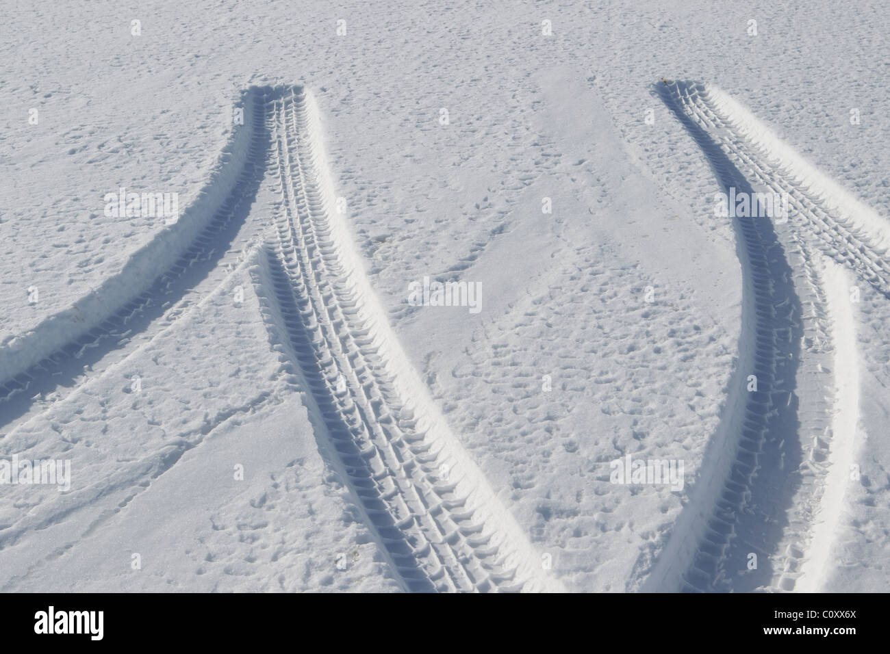Tire tracks in the snow record the evidence of backing and leaving. - Stock Image
