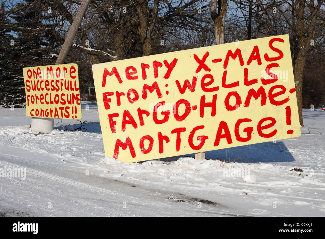 Hand painted signs in front of a USA foreclosed home indicating displeasure with the mortgage company - Stock Image