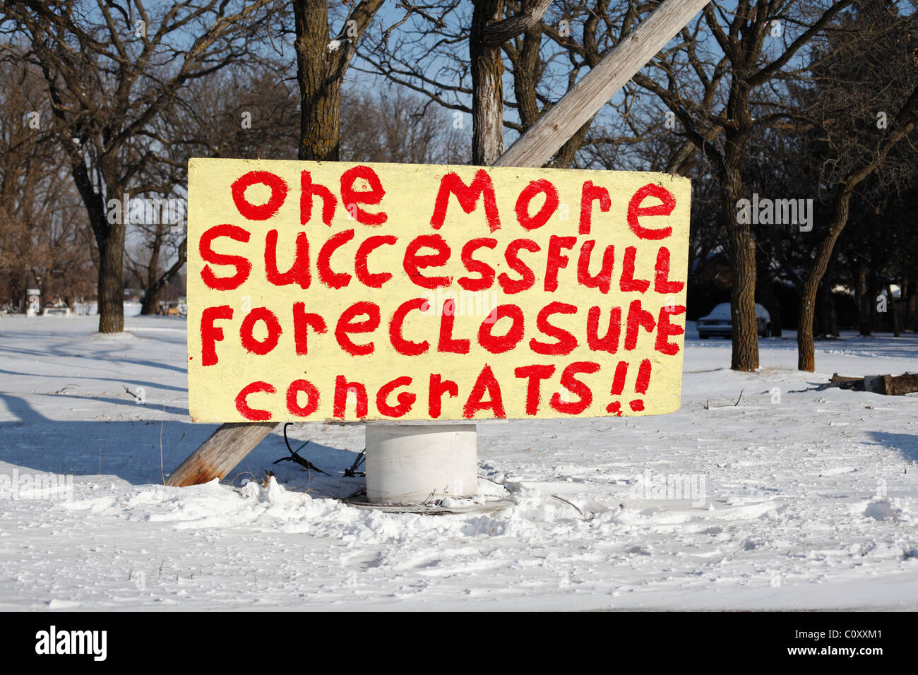 A hand painted sign in front of a USA foreclosed home sarcastically targeting the mortgage company. - Stock Image