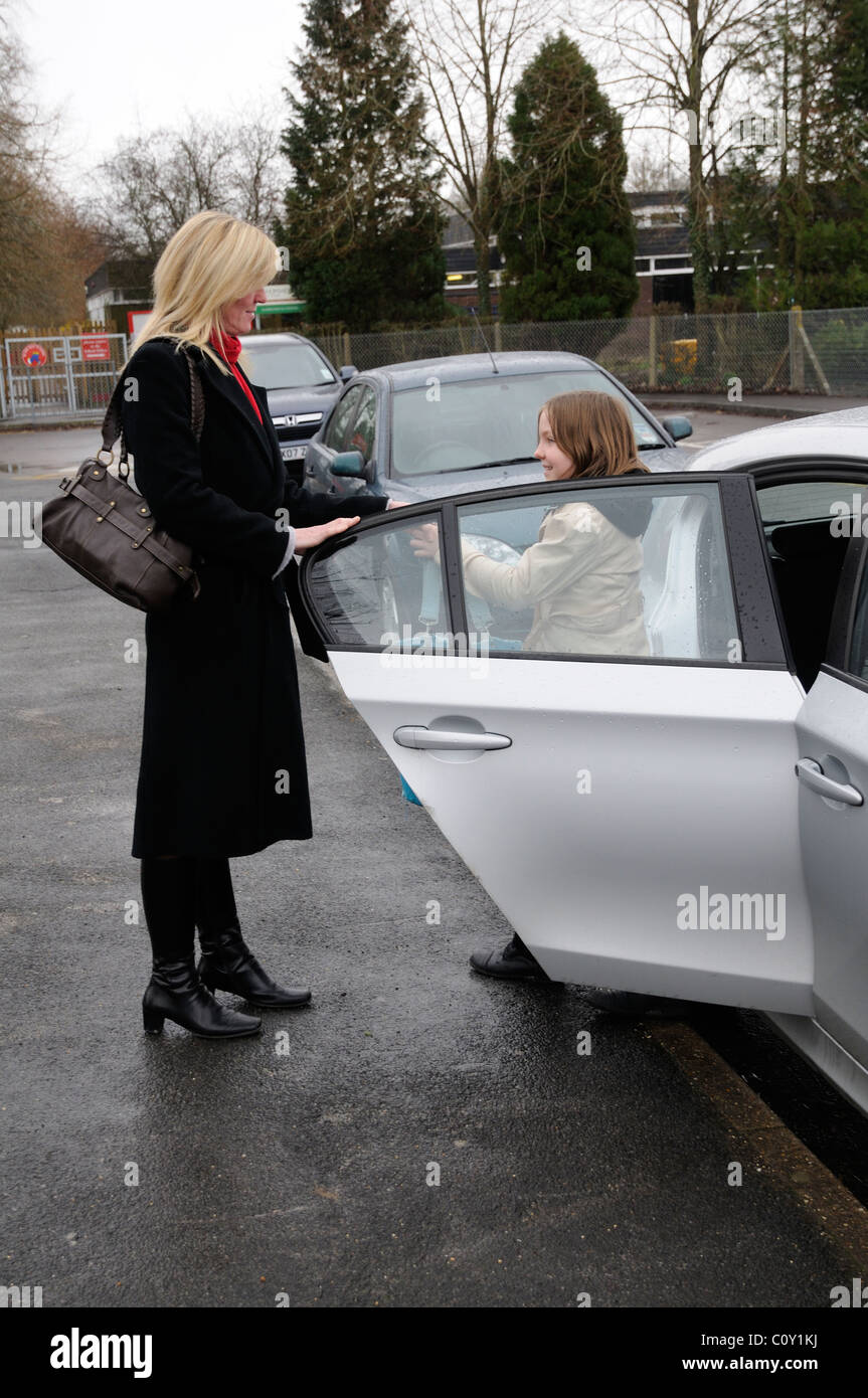Mother delivering her daughter to school by car - Stock Image
