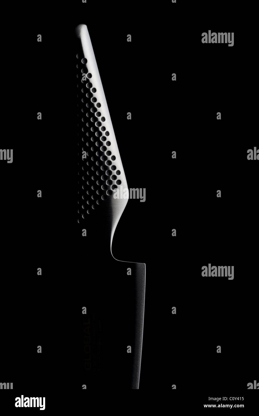 Studio shot of a Global knife handle and blade against a black background - Stock Image