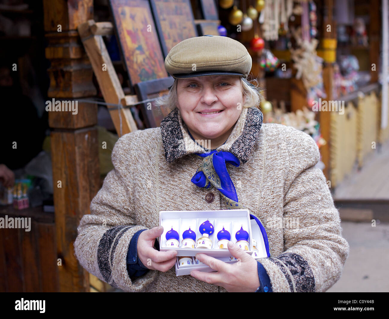 This Muscovite stallholder in Izmaylovo market  sells her hand-carved and painted traditional wood Christmas decorations, - Stock Image