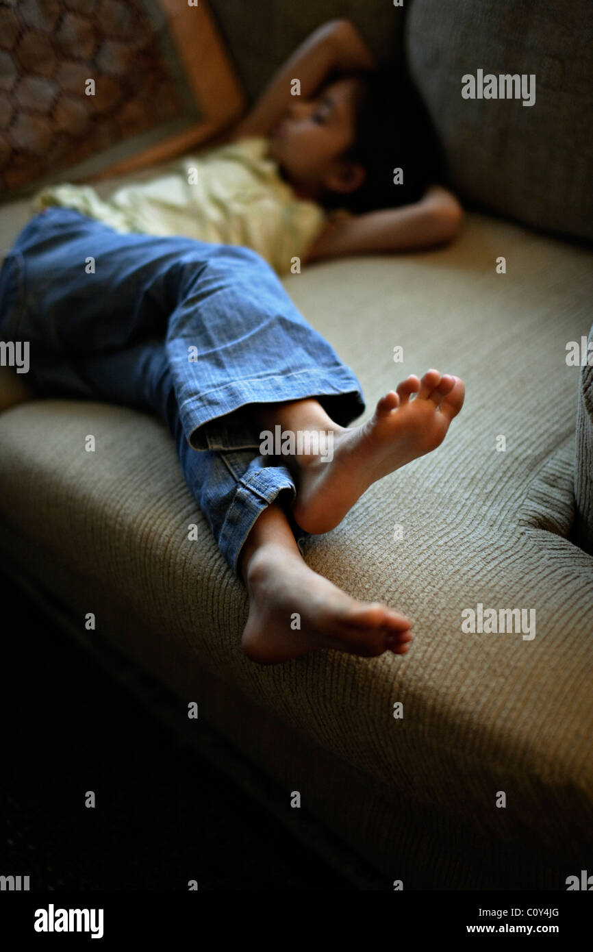 Barefoot girl lying on sofa. - Stock Image