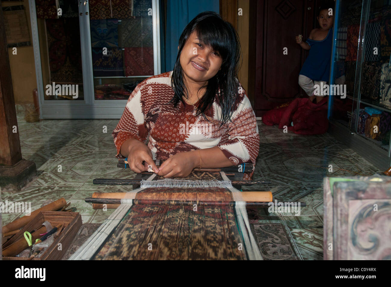 Woman doing traditional ikat weaving in the aboriginal Aga village of Tenganan in eastern Bali Stock Photo