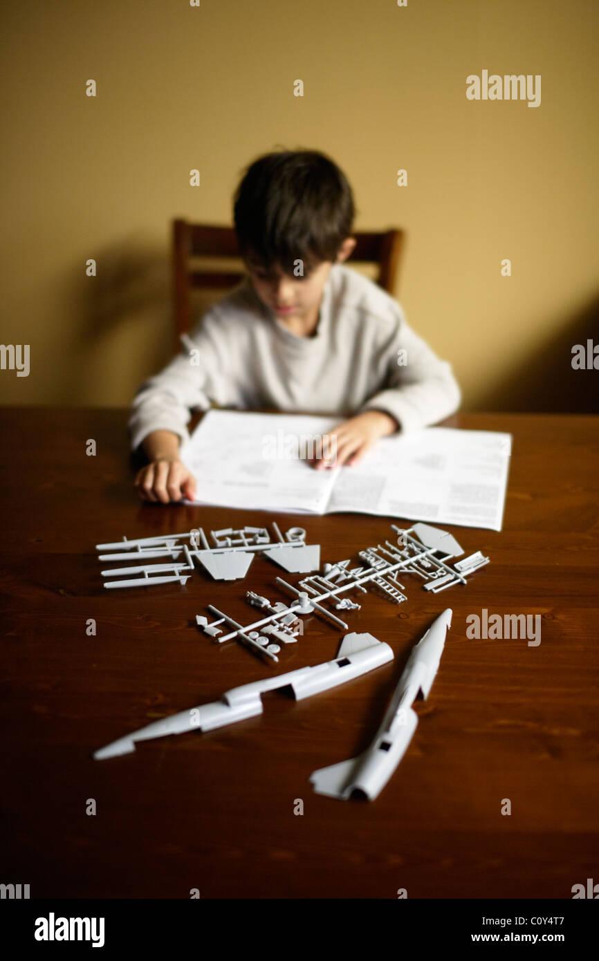 Boy with plastic kit set model aeroplane. - Stock Image