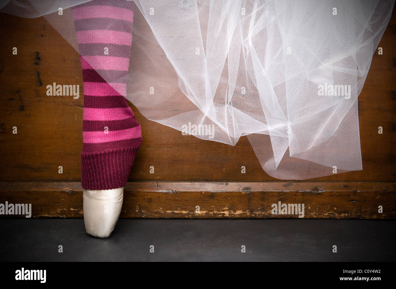 Detailed portrait of a ballerina's white tutu with point shoes and red striped stockings. - Stock Image
