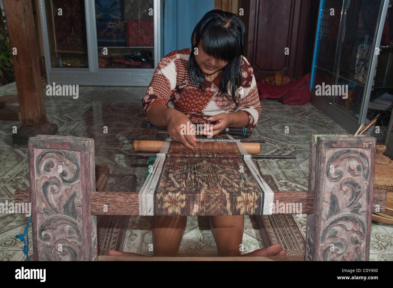 Woman doing traditional ikat weaving in the aboriginal Aga village of Tenganan in eastern Bali - Stock Image
