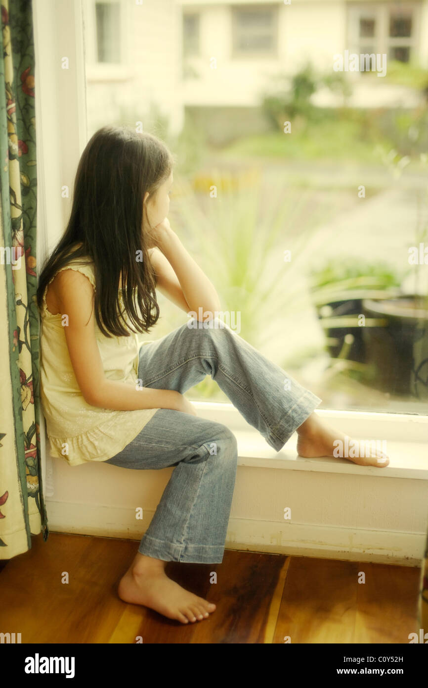 Girl sits by window on rainy day - Stock Image