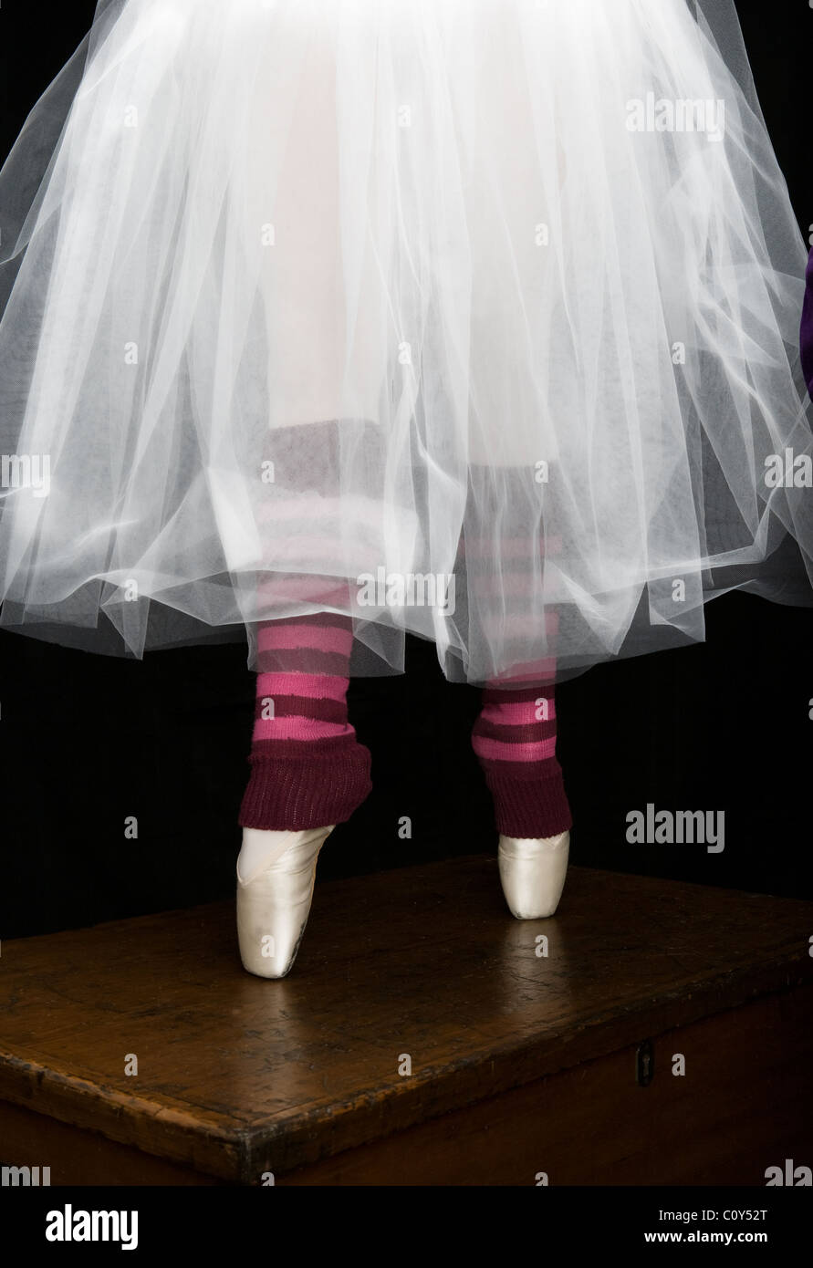 Detail portrait of a teenage ballerina wearing a white tutu and point shoes as she standing on her toes on top of - Stock Image