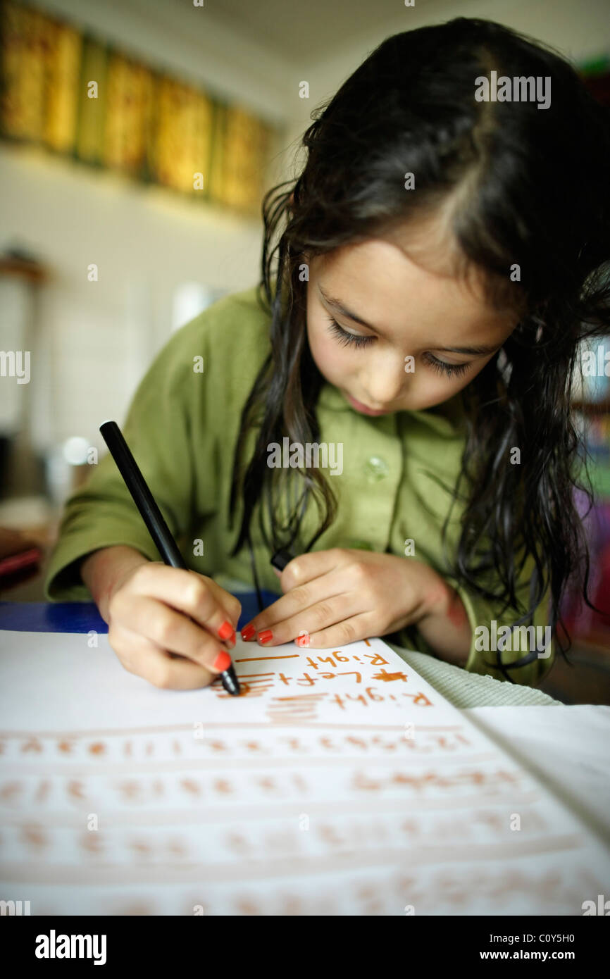 Girl writing. Child does her music theory homework. - Stock Image