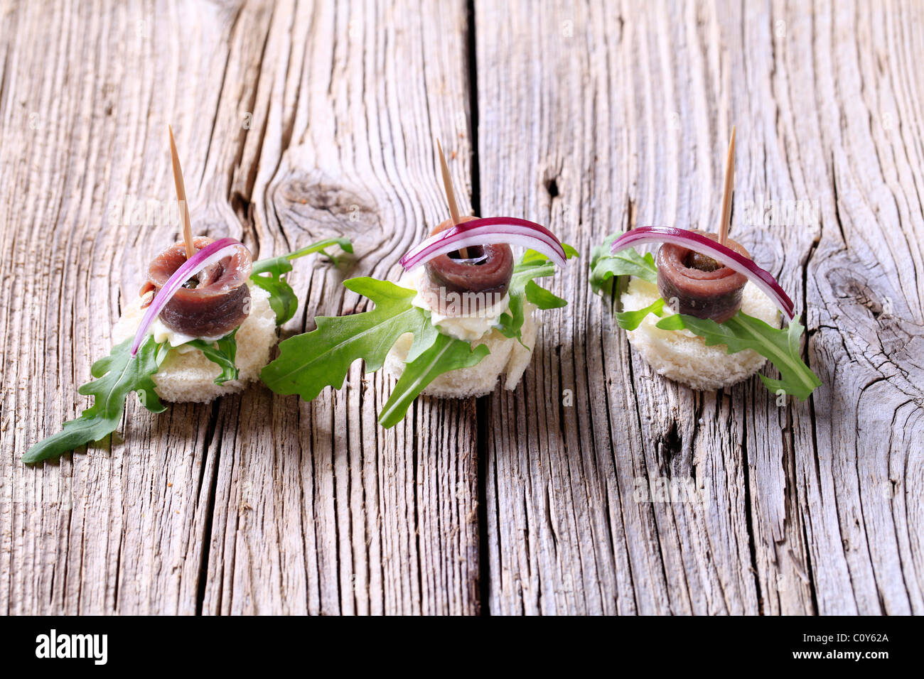 Anchovy canapes garnished with greens and onion - Stock Image