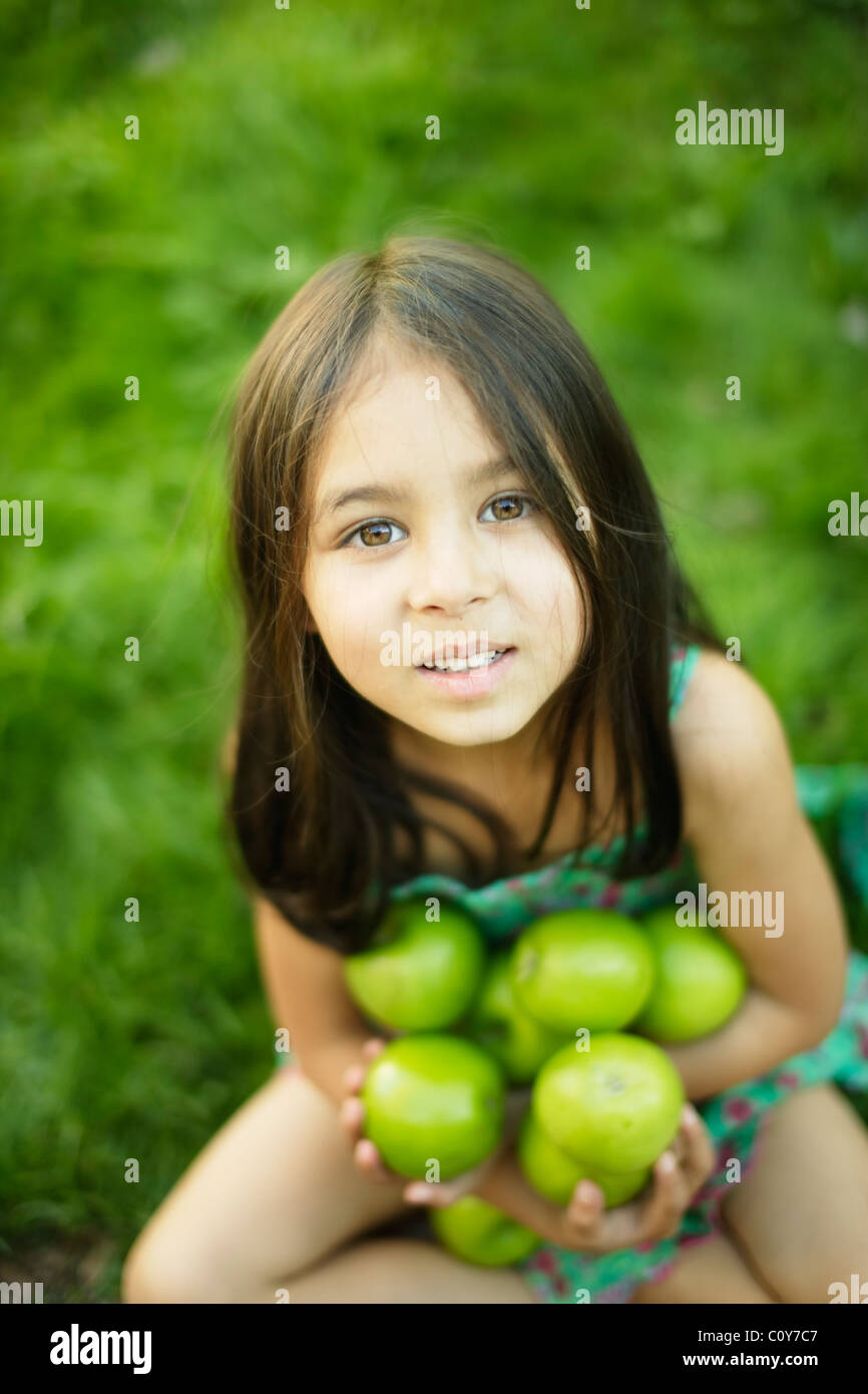 Six year old girl sits on grass lawn and holds green apples Stock Photo
