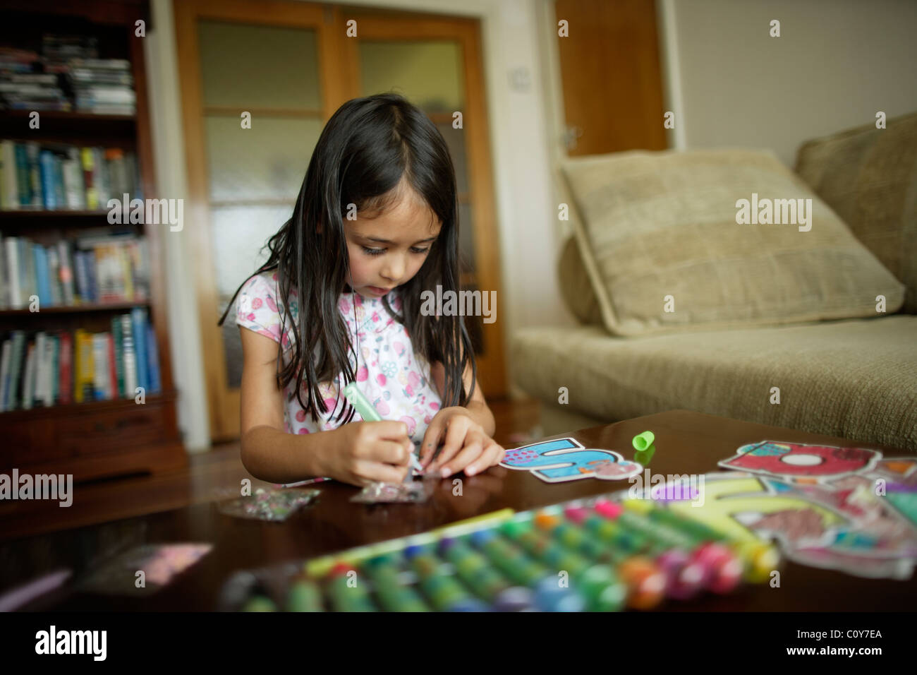 Six year old girl works on craft set of large letters to colour in and decorate - Stock Image