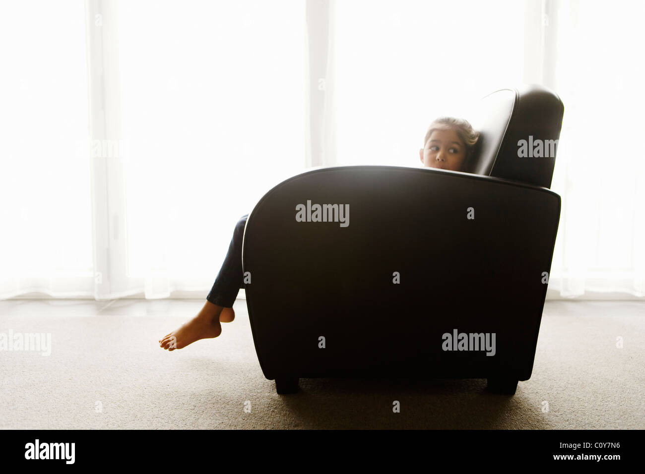 Six year old girl sits in art deco style armchair beside window. - Stock Image