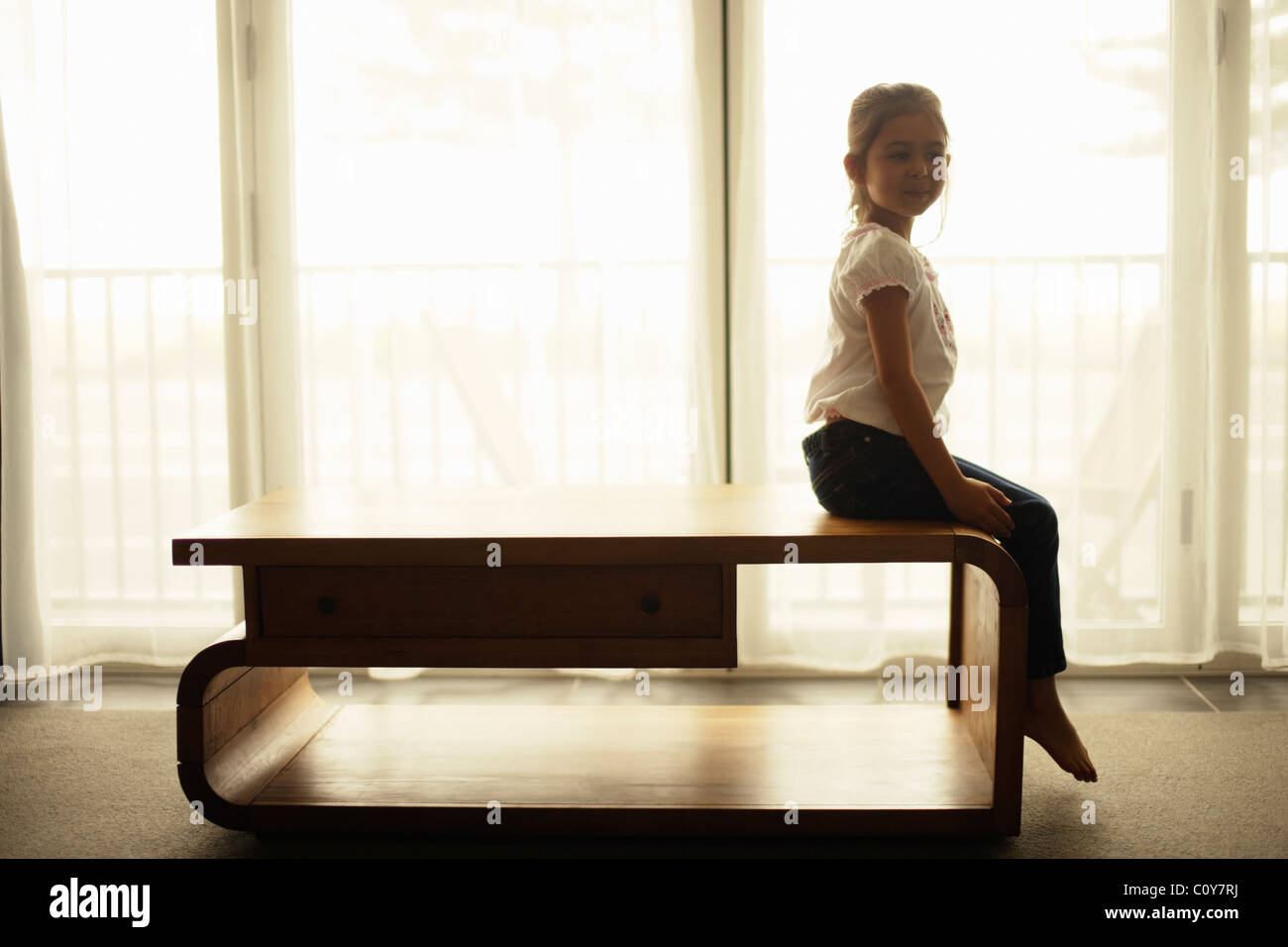 Girl sits on table beside window - Stock Image