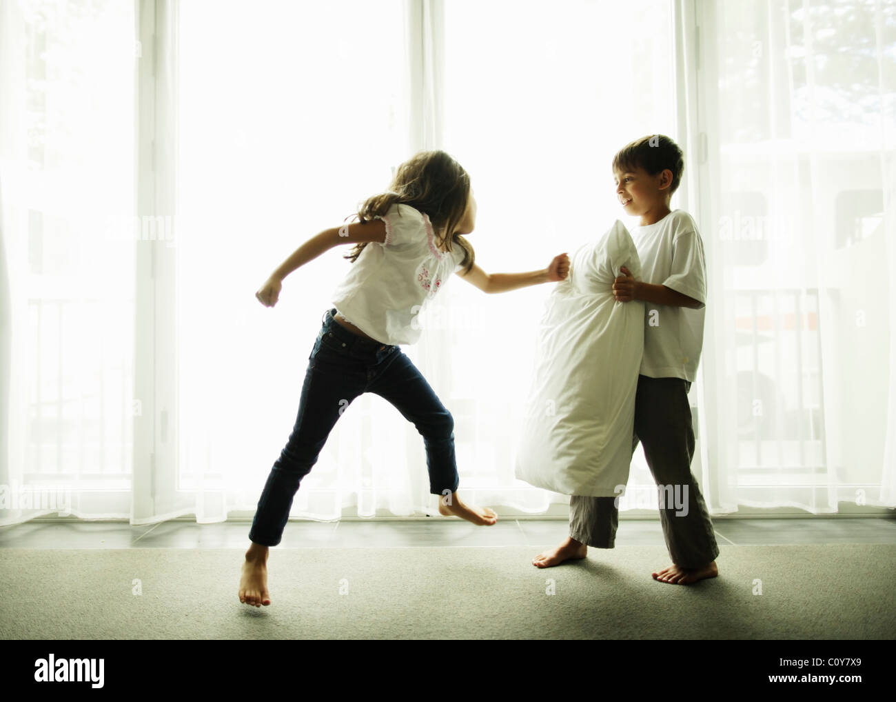 Boy holds pillow as punchbag for his kung fu sister. - Stock Image