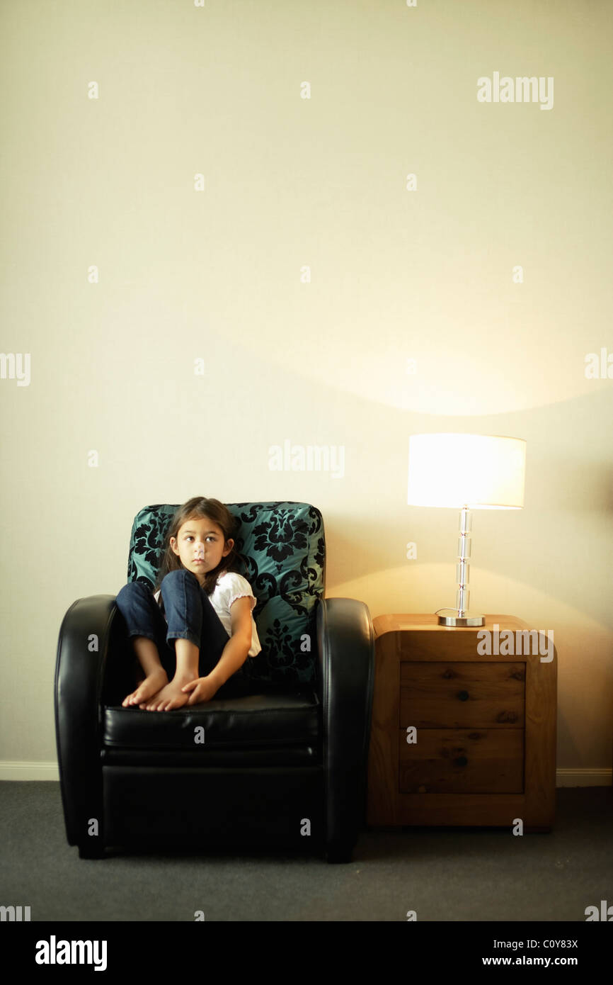 Girl sits in art deco style armchair with drawers and lamp - Stock Image