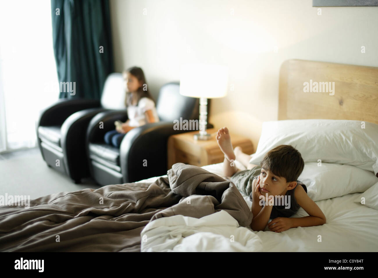 Boy on bed and girl in chair, watching wall mounted tv in a motel room. - Stock Image