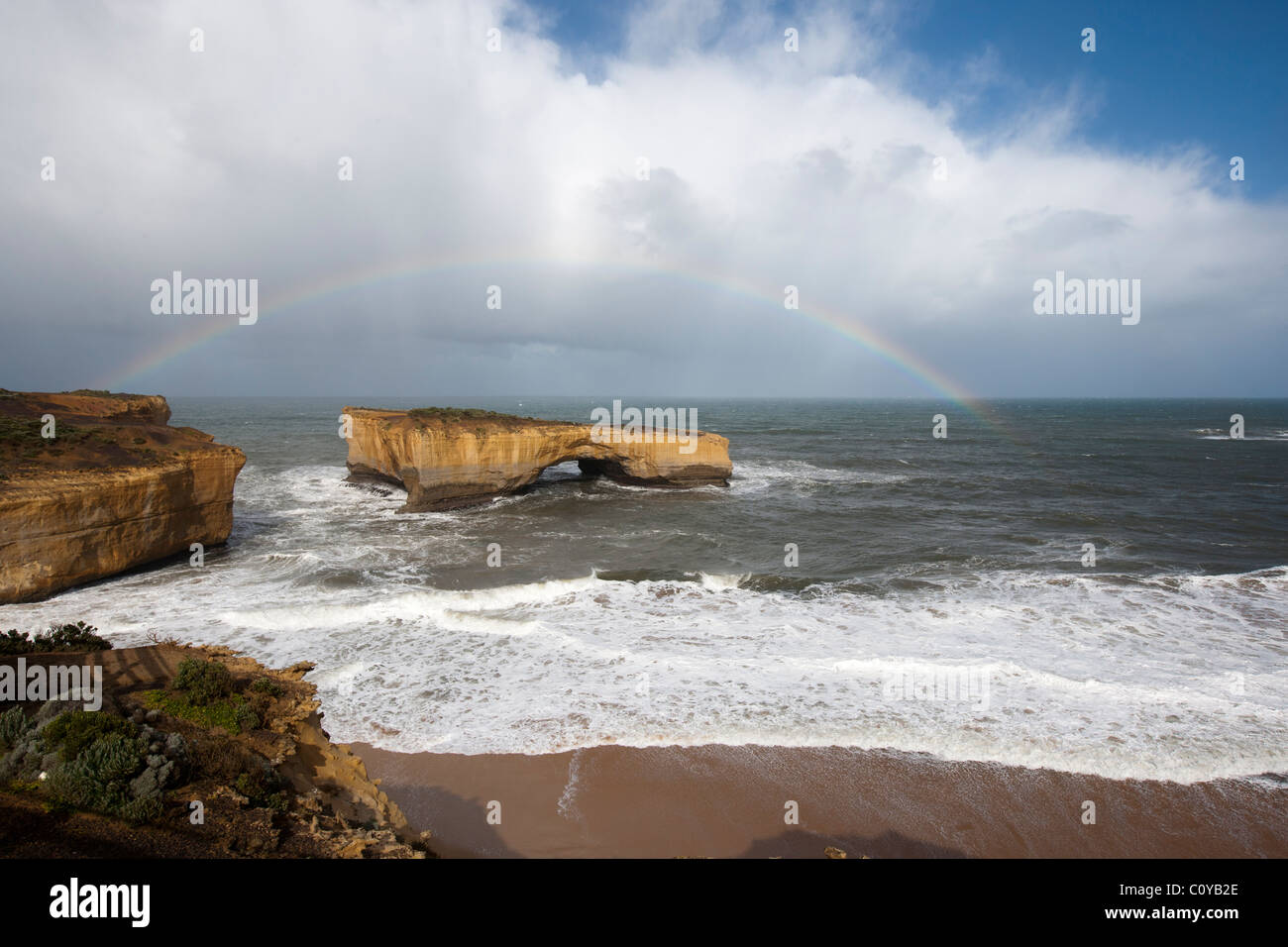 London arch, formerly London bridge before the collapse, surrounded by rainbow. Great Ocean Road, Victoria, Australia - Stock Image