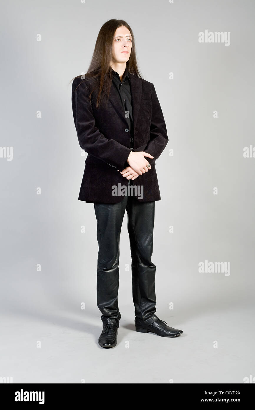 Portrait of the young long-haired man in a suit - Stock Image