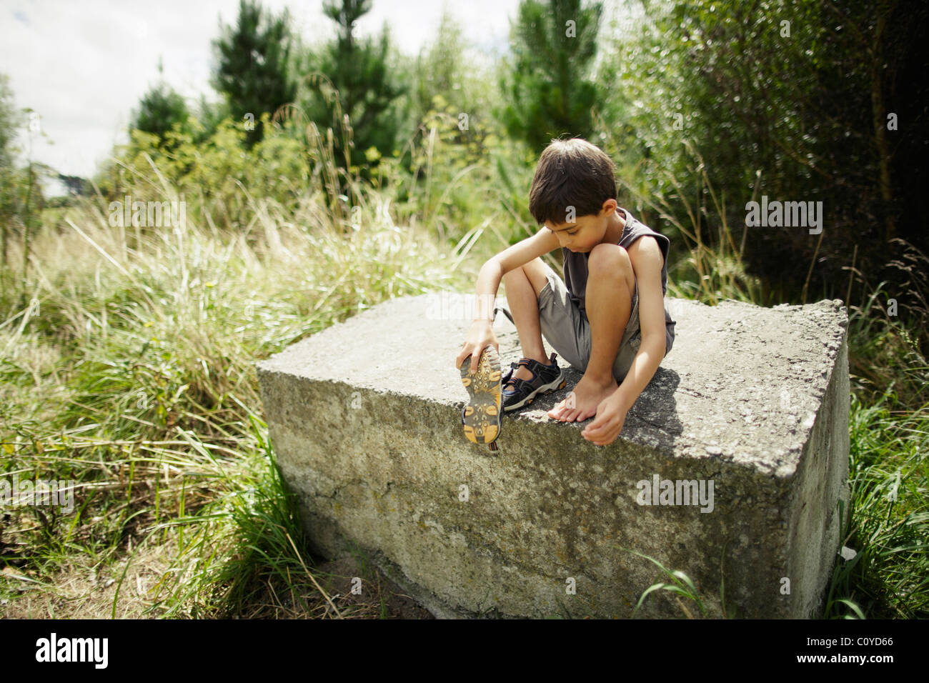 Boy sits on concrete block and gets stone out of shoe - Stock Image