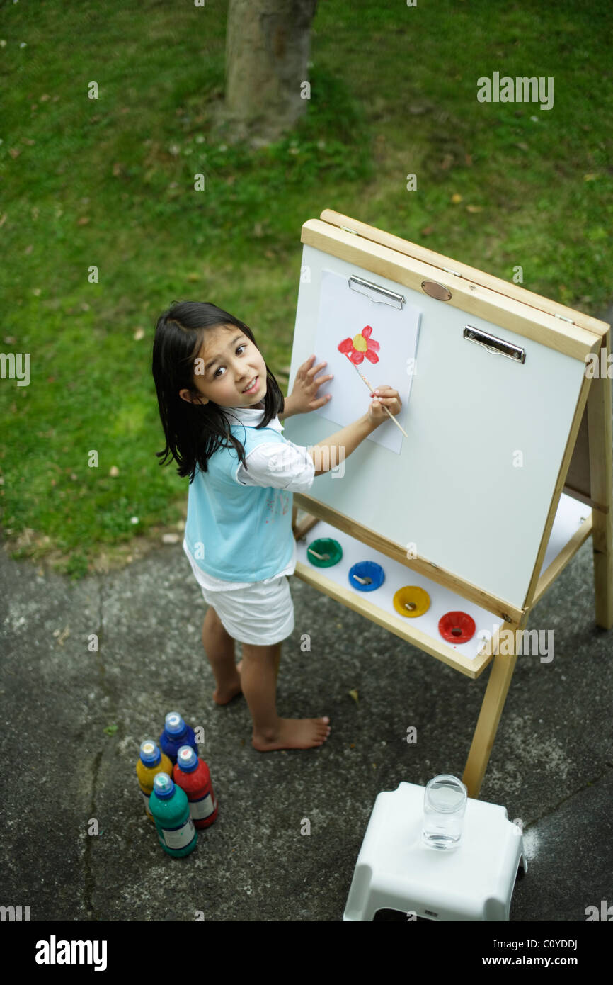 Girl painting on easel in back yard. - Stock Image