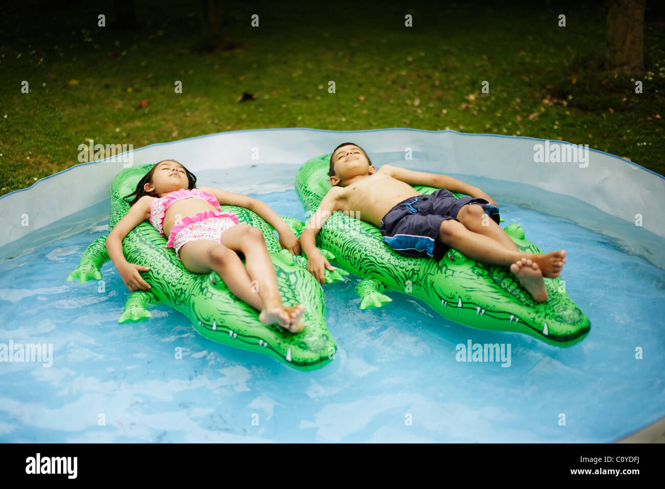 Boy and girl lie on inflatable crocodiles floating in paddling pool. - Stock Image