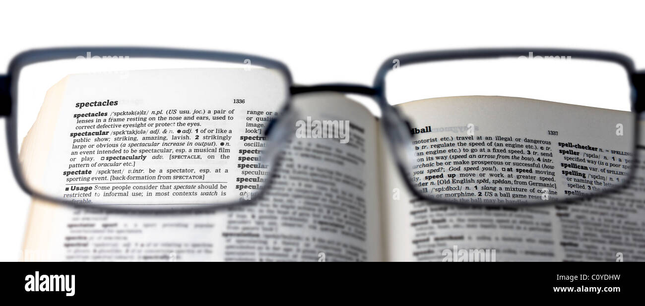 Reading a dictionary with spectacles to read the definition of 'spectacles' - Stock Image