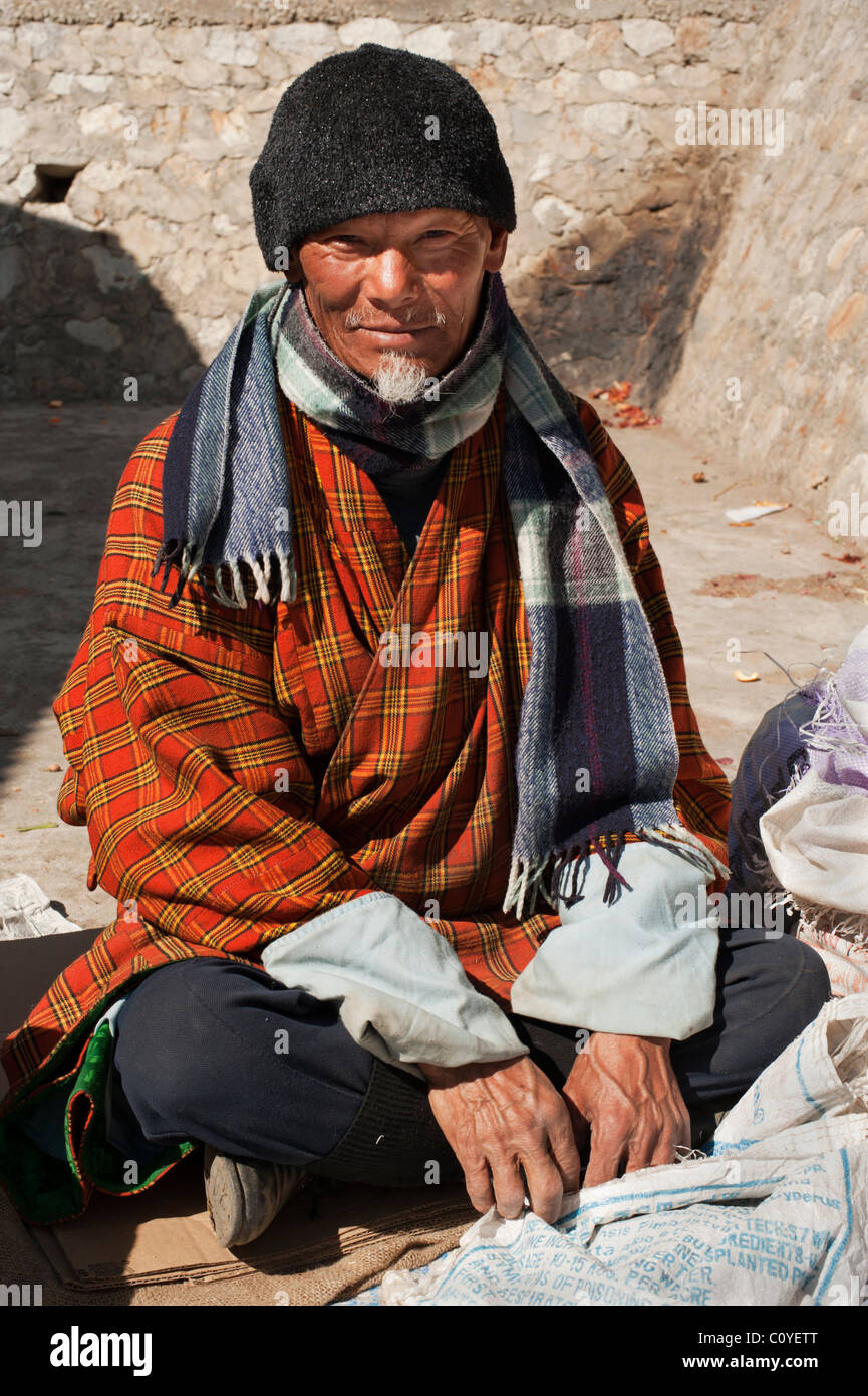 Elderly Bhutanese man with goatee selling his wares in the Paro market, Bhutan. - Stock Image