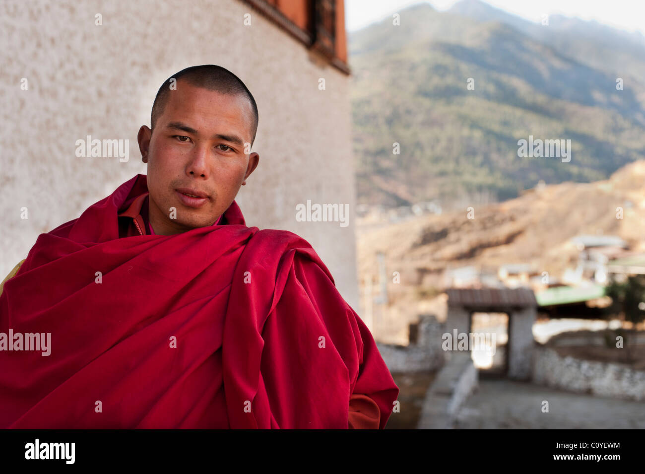 Young Buddhist monk standing outside the Paro Dzong with the Himalayas in the background - Stock Image