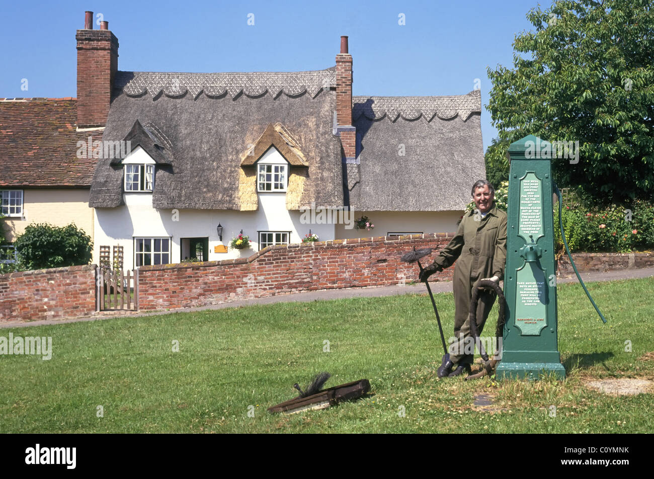 Chimney sweep posing beside historical water pump on Monks Eleigh village green property name beyond digitally removed - Stock Image