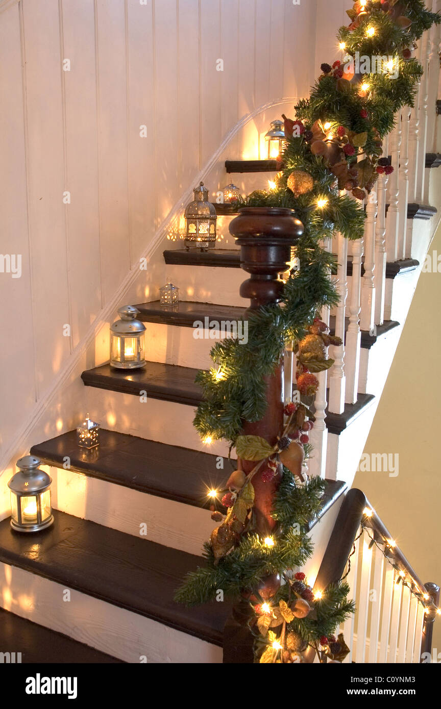 lanterns and christmas garlands adorn a wooden staircase and banister stock image