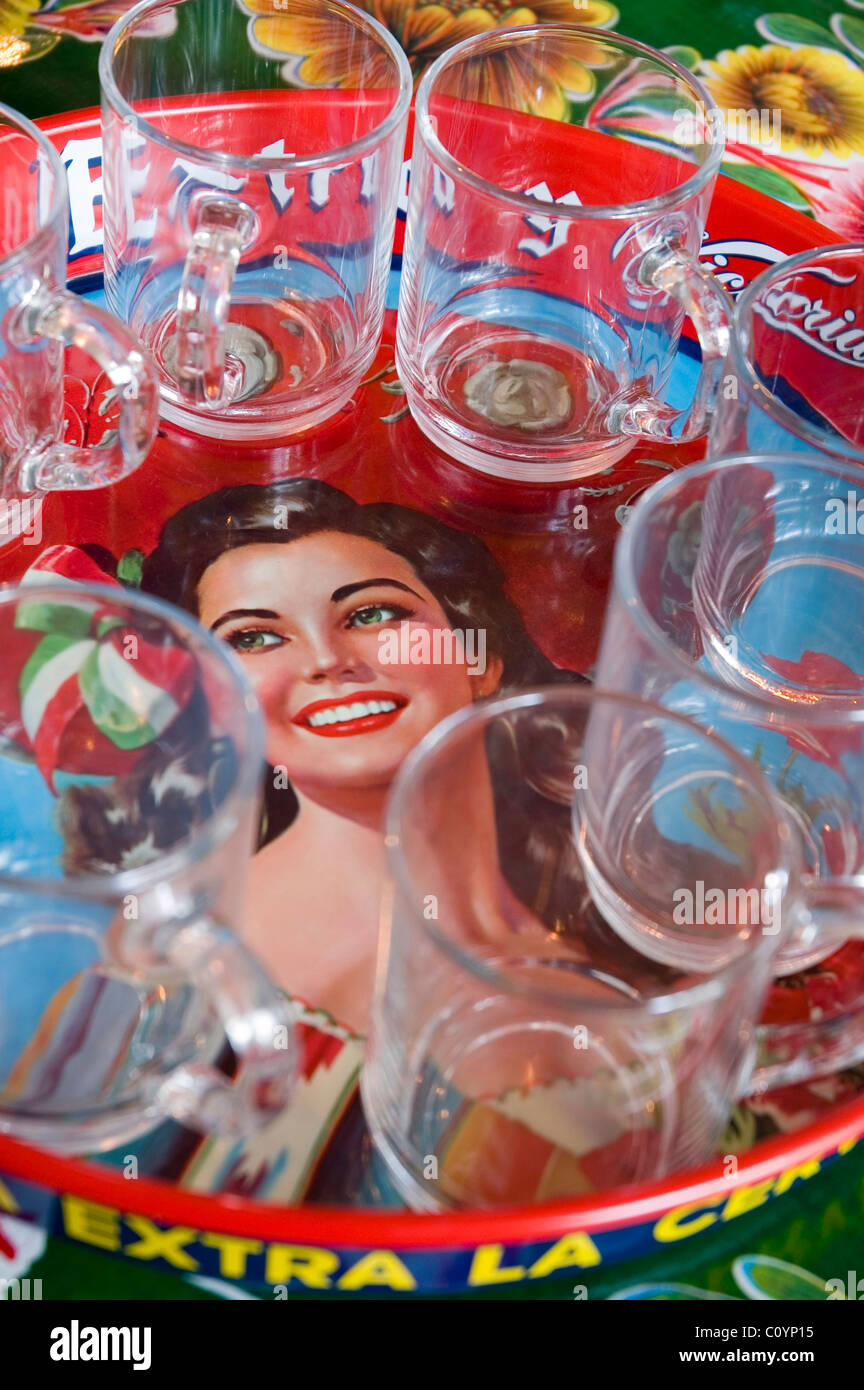 Glass teacups on a vintage mexican beer tray - Stock Image