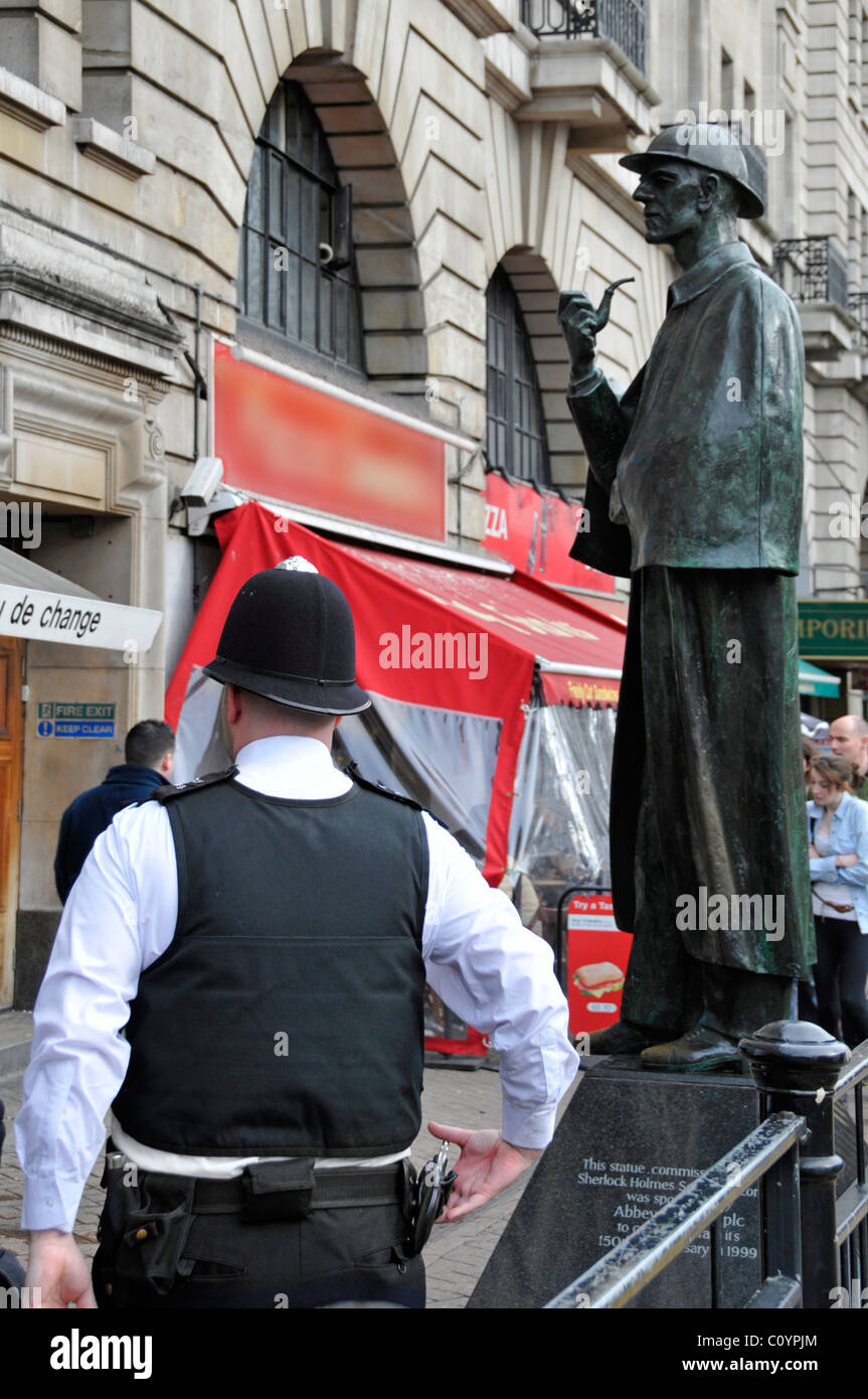Beat policeman patrolling tourist area outside Baker Street Station with Sherlock Holmes sculpture beyond obscured - Stock Image