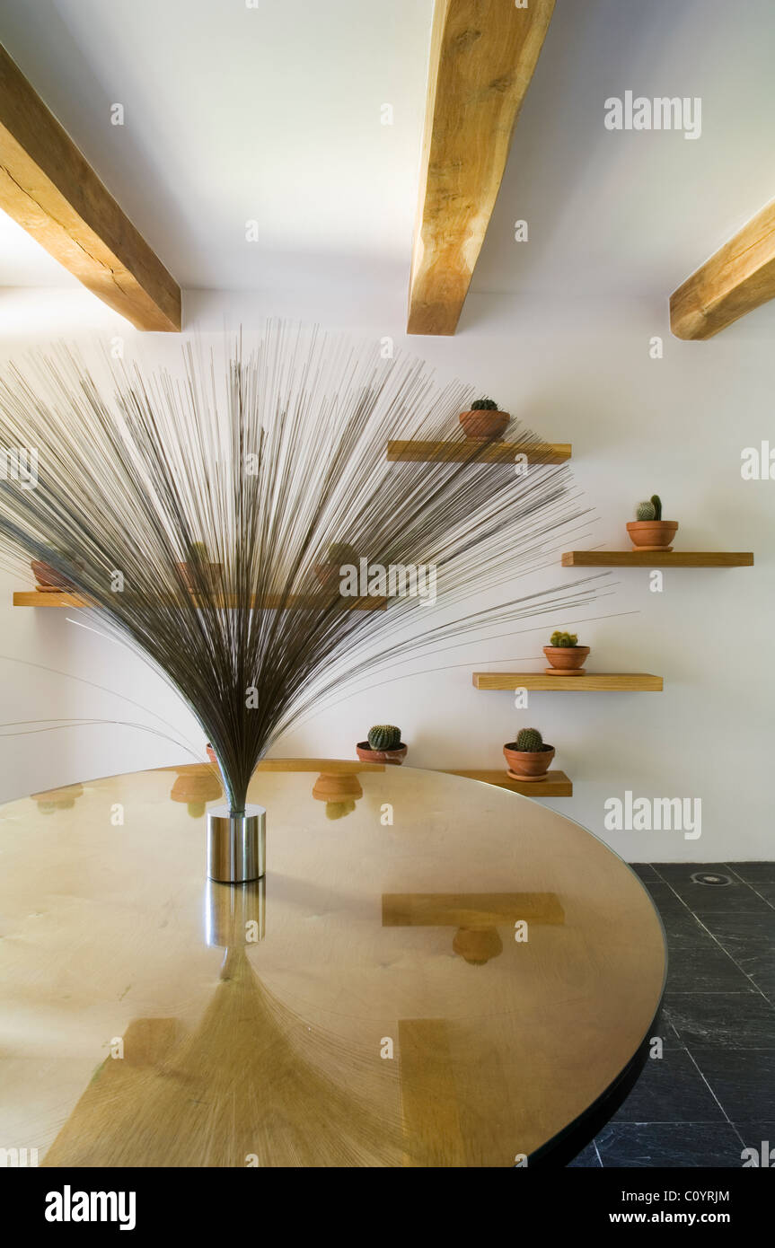 Harry Bertoia spray sculpture on a glass topped oval Gerald Summers table in white room with beamed ceiling and - Stock Image