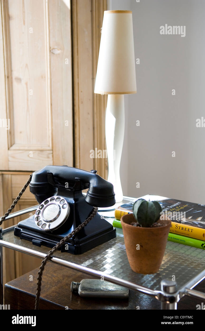 Old rotary bakelite telephone on side table with potted cactus plant and lamp - Stock Image