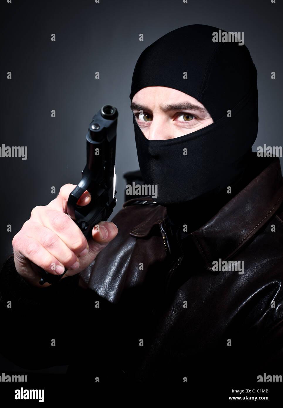 fine closeup portrait of criminal holding pistol - Stock Image