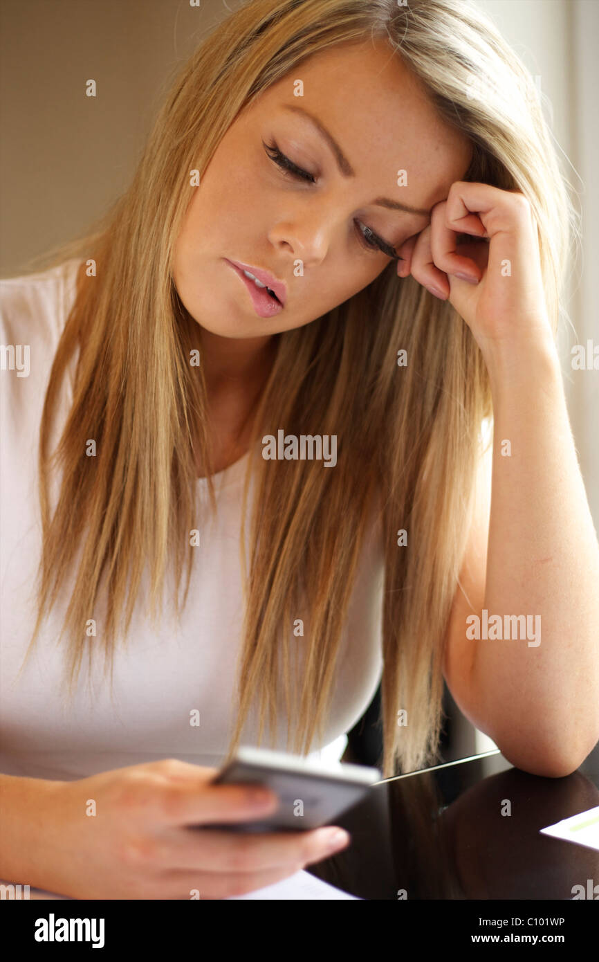 young female holding a calculator looking worried working out her finances - Stock Image
