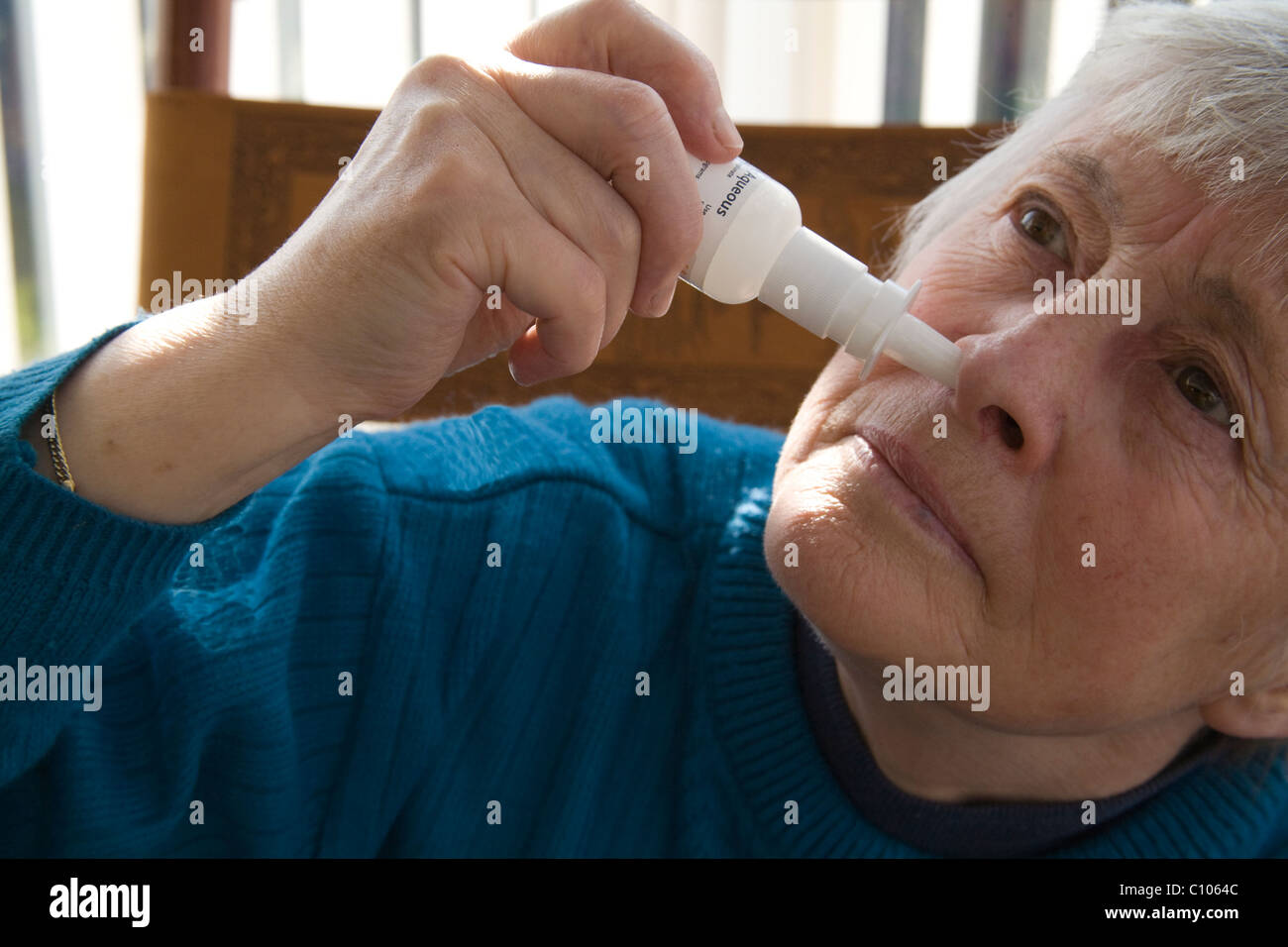Close up elderly woman using a nasal spray to relieve symptoms of hay fever Stock Photo