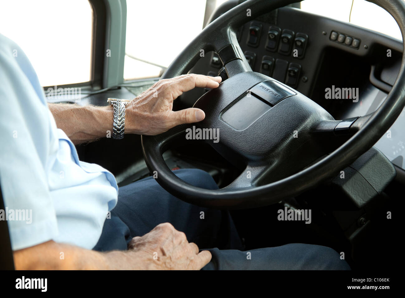 Bus driver's hand on steering wheel USA - Stock Image
