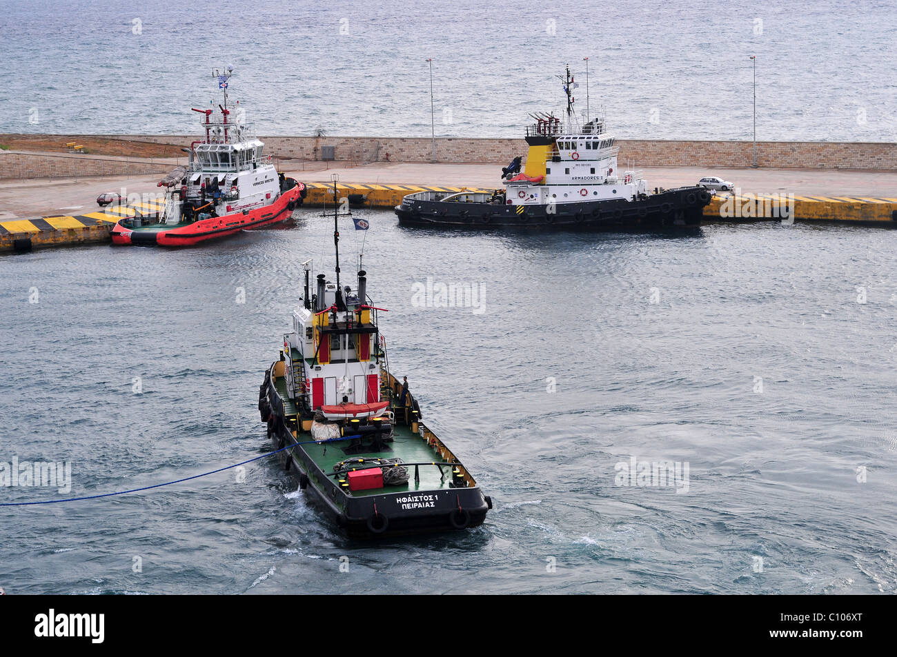 Three tugs waiting near the harbour breakwater at Pireas, Athens, Greece. - Stock Image