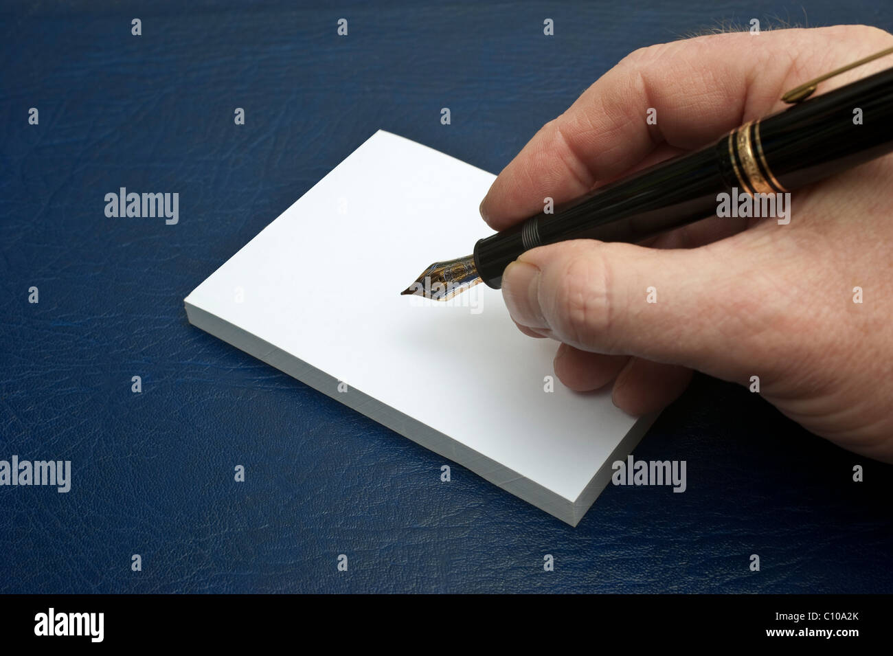 A male hand holding a Mont Blanc Meisterstuck 149 fountain pen about to write on a white writing pad - Stock Image