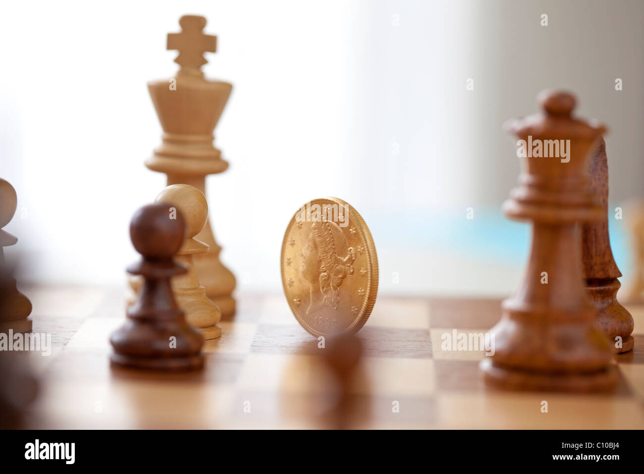 gold coin player in chess game - Stock Image
